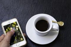 Una taza de café express y de mobille Foto de archivo