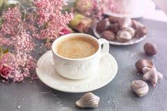 Una taza de café fragante por la mañana y un ramo de flores rosadas Dulces del chocolate bajo la forma de conchas de berberecho C foto de archivo libre de regalías