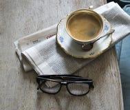 Una taza de café fuerte aromático en un platillo con una cuchara del vintage Periódico y vidrios en la tabla imagen de archivo libre de regalías