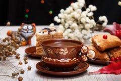 Una taza de café, de galletas de la fruta, de torta y de una figura de un gato rojo en la tabla Fondo blanco Planta del lino seca imágenes de archivo libres de regalías