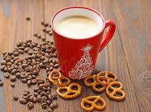 Una taza de café, granos del café y galletas en una tabla de madera imagenes de archivo
