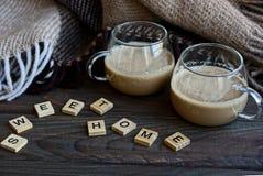 Una taza de café una manta de lana en la tabla con una palabra del hogar de madera del dulce de las letras Imágenes de archivo libres de regalías