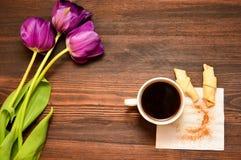 Una taza de café o de té con un cruasán en una servilleta se coloca en un fondo de madera, al lado de ella es tulipanes púrpuras imagen de archivo