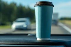 Una taza de café de papel azul en la consola del coche imagen de archivo