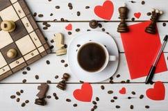 Una taza de café, pedazos de ajedrez y el concepto de amor Imagenes de archivo