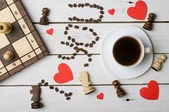 Una taza de café, pedazos de ajedrez y el concepto de amor Imagen de archivo libre de regalías