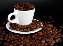 Una taza de café por completo de granos de café imágenes de archivo libres de regalías