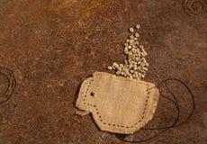 Una taza de café por completo de los granos de café crudos Imagen de archivo libre de regalías