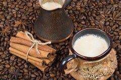 Una taza de café, de pote y de canela recientemente preparados en los granos de café Imágenes de archivo libres de regalías