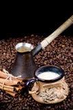 Una taza de café, de pote y de canela recientemente preparados en los granos de café Fotografía de archivo