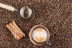 Una taza de café, de pote y de canela recientemente preparados en los granos de café Imagen de archivo
