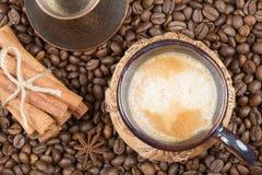 Una taza de café, de pote y de canela recientemente preparados en los granos de café Foto de archivo libre de regalías