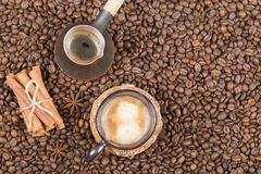 Una taza de café, de pote y de canela recientemente preparados en los granos de café Fotografía de archivo libre de regalías