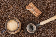 Una taza de café, de pote y de canela recientemente preparados en los granos de café Fotos de archivo