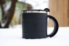 Una taza de café que consigue frío en la nieve Fotos de archivo