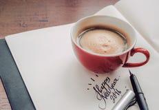 Una taza de café que descansa sobre un libro con la Feliz Año Nuevo 2016 del texto Foto de archivo