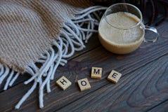 Una taza de café que una manta de lana en la tabla con una palabra de letras de madera se dirige Fotos de archivo