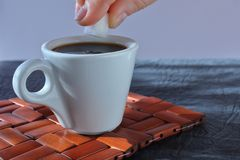 Una taza de café que vigoriza aromático de la mañana en un soporte de madera de mimbre fotografía de archivo