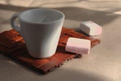 Una taza de café que vigoriza aromático de la mañana en un soporte de madera de mimbre imagen de archivo