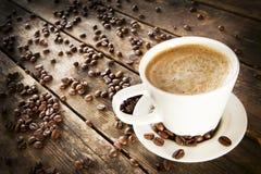 Una taza de café rodeada por los granos de café. Imagen de archivo
