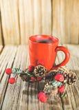 Una taza de café roja con el ornamento de la Navidad en la vieja sobremesa de madera con el fondo de madera del panel Imagen de archivo libre de regalías