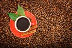 Una taza de café roja se coloca en los granos del café frito Foto de archivo