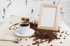 Una taza de café sólo con los granos del canela y de café en una tabla de madera foto de archivo