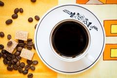Una taza de café sólo, de azúcar marrón y de granos de café Foto de archivo libre de regalías