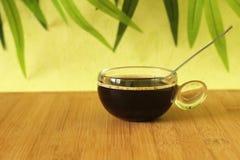 Una taza de café sólo en un piso de madera de bambú marrón con una cuchara en un fondo verde del follaje Foto de archivo
