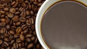 Una taza de café sólo sobre los granos de café asados fotografía de archivo libre de regalías