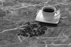Una taza de caf? s?lo y los granos mienten en una tabla de m?rmol tiro blanco negro imágenes de archivo libres de regalías