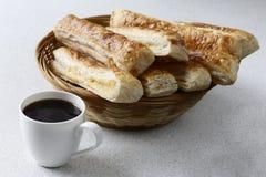 Una taza de café sólo y una cesta de mimbre con las galletas hechas en casa Imagen de archivo libre de regalías