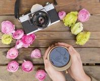 Una taza de café sostenida en dos manos en una tabla de madera con una cámara clásica de la foto alrededor con las flores colorid Fotos de archivo
