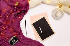Una taza de café, de un pequeño tablero de madera negro y de una tiza blanca con metas de los Años Nuevos Luces de la bufanda y d Imagen de archivo libre de regalías