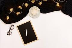 Una taza de café, de un pequeño tablero de madera negro y de una tiza blanca con metas de los Años Nuevos Luces de la bufanda y d Foto de archivo libre de regalías