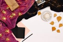 Una taza de café, de un pequeño tablero de madera negro y de una tiza blanca con metas de los Años Nuevos Luces de la bufanda y d Imagen de archivo