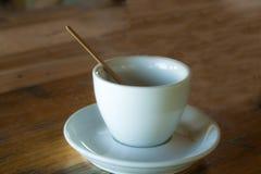 Una taza de café vacía y un palillo se colocan en una tabla Fotos de archivo