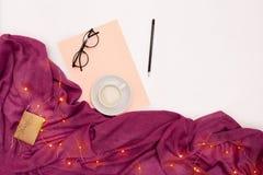 Una taza de café, vidrios negros, papel rosado con metas de los Años Nuevos Luces de la bufanda y de la Navidad en el fondo blanc Fotografía de archivo