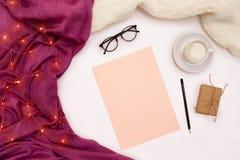 Una taza de café, vidrios negros, papel rosado con metas de los Años Nuevos Luces de la bufanda y de la Navidad en el fondo blanc Imagen de archivo libre de regalías