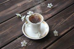 Una taza de café y de cereza florece en la tabla de madera Foto de archivo
