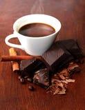 Una taza de café y de chocolate oscuro con canela imagen de archivo