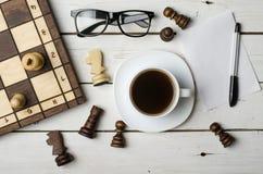 Una taza de café y de pedazos de ajedrez calientes en una tabla de madera, visión superior Imagen de archivo libre de regalías
