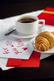 Una taza de café y de un cruasán Foto de archivo