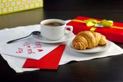 Una taza de café y de un cruasán Foto de archivo libre de regalías