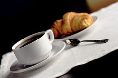 Una taza de café y de un cruasán Fotos de archivo libres de regalías