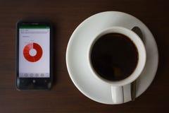 Una taza de café y de un smartphone Foto de archivo