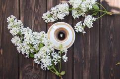 Una taza de café y de una rama de lilas en una tabla de madera Fotografía de archivo libre de regalías