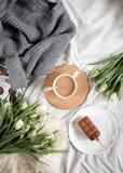 Una taza de café y de una torta en un mantel acogedor Fotografía de archivo