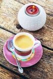 Una taza de café y de una vela ardiente en una palmatoria en un fondo de madera Fotos de archivo
