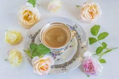 Una taza de café y de varias rosas rosadas Foto de archivo libre de regalías